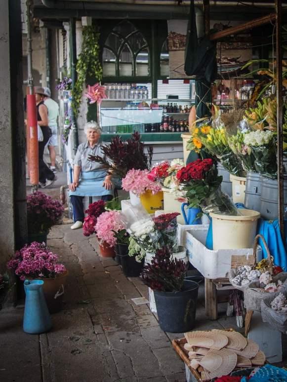 des fleurs et une vielle dame au marche do bolhao a porto voyage portugal