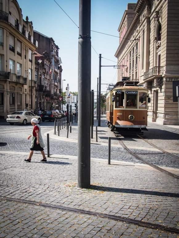 vieille dame traversant a pied devant le vieux tramway en bois a porto voyage portugal