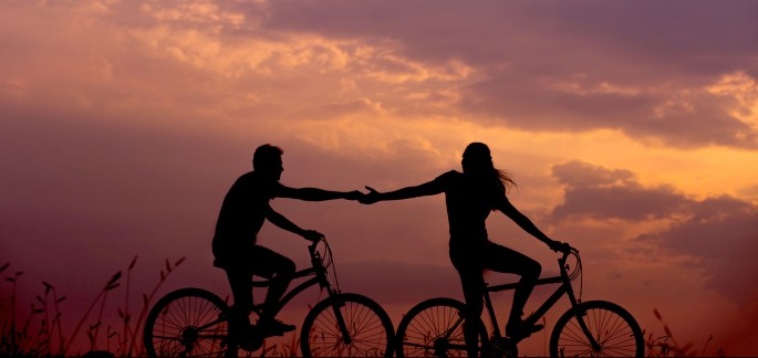 An adventurous couple ride bikes in the sunset, holding hands, symbolizing their aliveness, intimacy and connection.