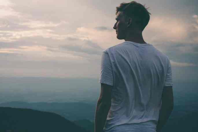 An attractive single man looks out across an expansive view, symbolizing his own viewing point