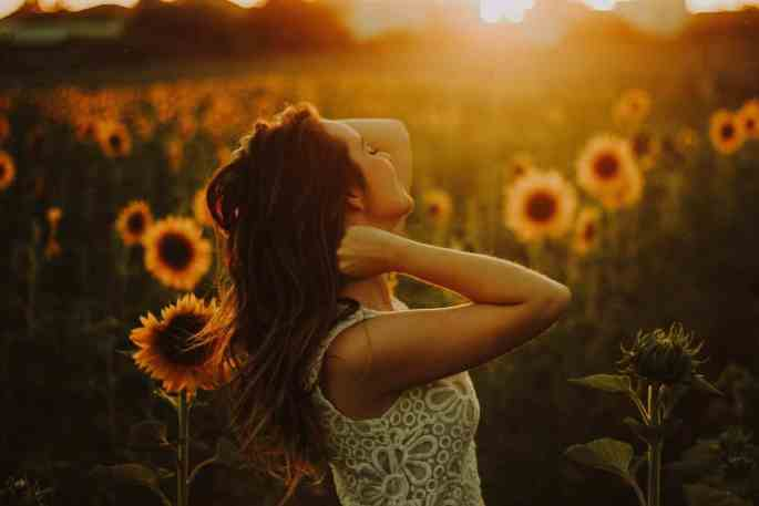 An attractive woman opens her heart to love, celebrating her sensuality in the light of the sun in a field of sunflowers