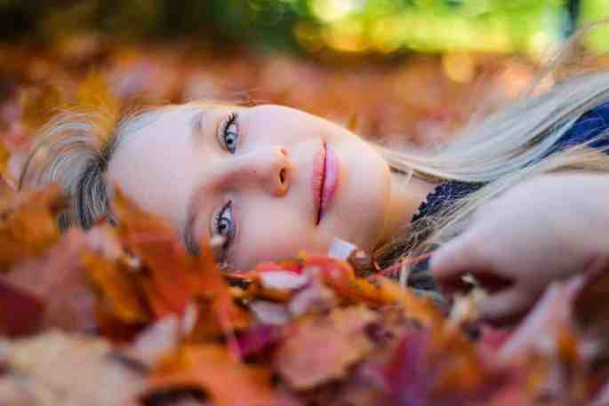 A woman lies in autumn leaves in a state of self acceptance and self intimacy.