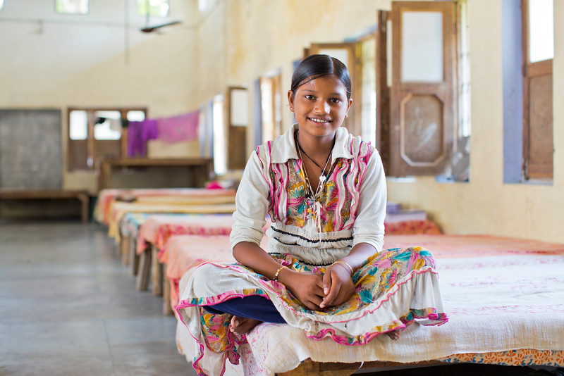 "Laxmi Pal, 12 years old, sits on her bed in the Udaan Girls School in Hardoi, India. She was a featured girl in CARE's ""International Day of the Girl"" art exhibition in Atlanta, GA. The Udaan Girls School provides girls with a core curriculum in language, math, and environmental science subjects. Udaan teachers also interweave activities such as morning assembly, sports (volleyball, soccer), bicycle riding and computer usage. Photo by Josh Estey."