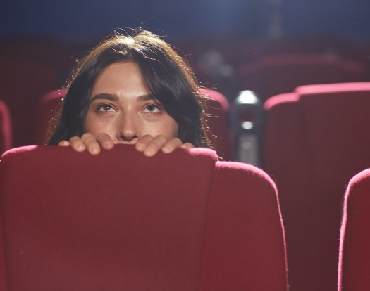 Chica observando la magia del cine desde una butaca