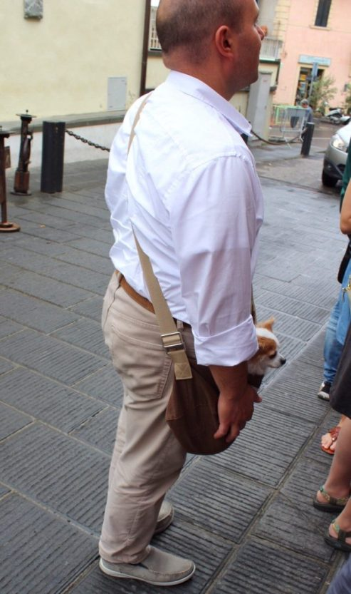 A guy standing outside of a shop in Italy