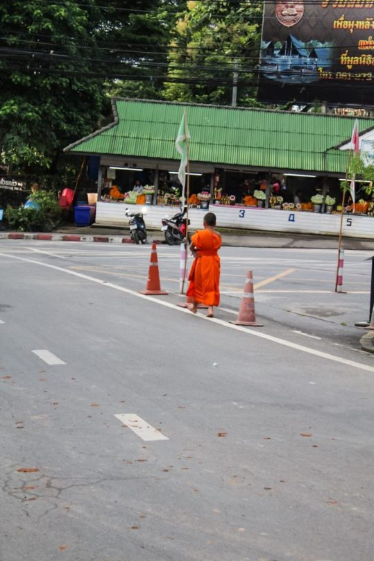 A young monk about to receive alms from the locals in Chiang Mai on our way to Wat Phra That Doi Suthep Chiang Mai