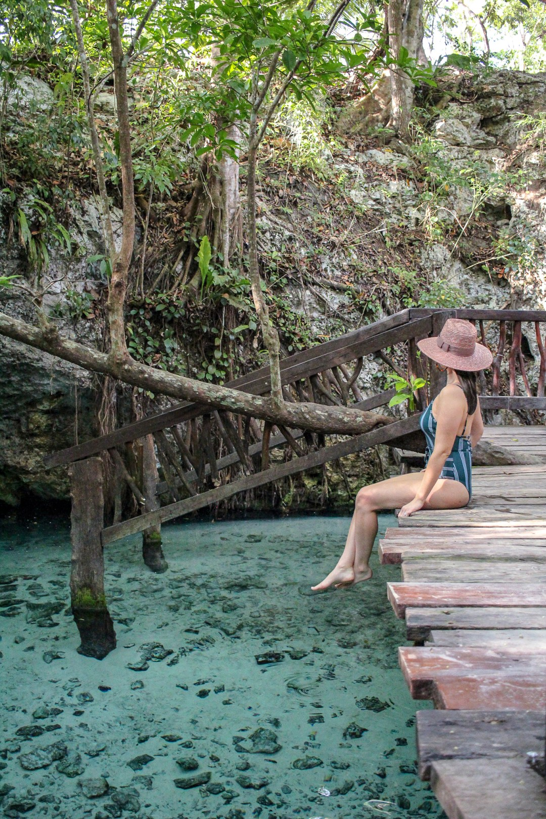 girl matching the grand cenote in tulum with pink hat