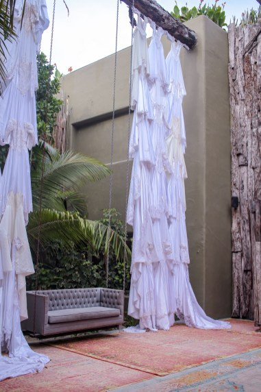 hanging couch in between hanging wedding dresses as part of an art installation