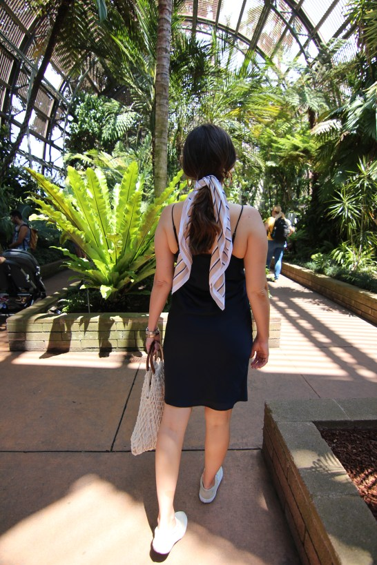 girl in botanical garden with hair scarf surrounded by greenery