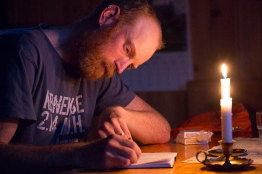 Emil skriver dagbok i stearinljussken