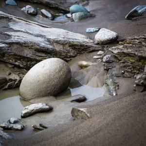 Sand och runda stenar