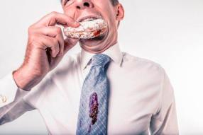 Man in suit devouring a cream cake
