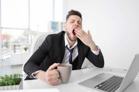 Man yawning at desk