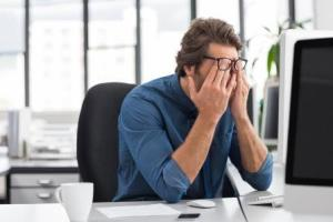 Demotivated man rubbing eyes at desk