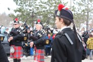 The Pipes and Drums lead the Swans down the street.
