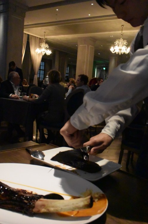 The waiter cutting the short-rib.