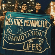 """Devon and Cat hold a banner """"Restore Meaningful Commutation for Lifers"""" at the Fight for 15 labor march."""