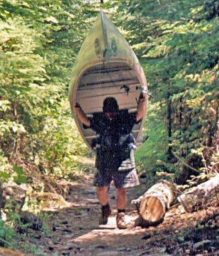 Russell Hoover, shoulder surgery patient, portages his canoe through the Boundary Waters of Minnesota and Canada.