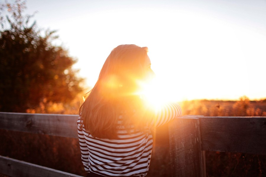 The back of a woman in striped top looking in the distance with the sun streaming in