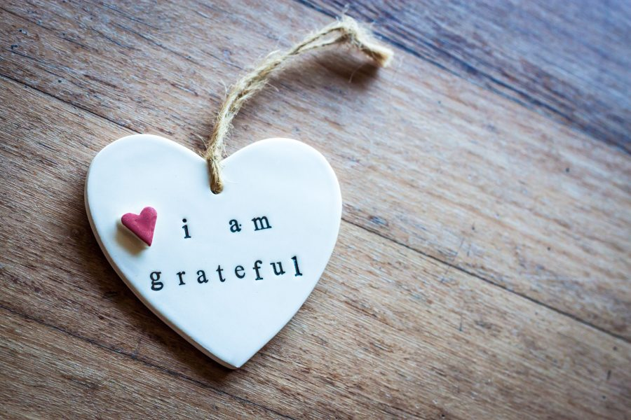 'I am grateful' written on a hanging white heart laid on a wooden surface