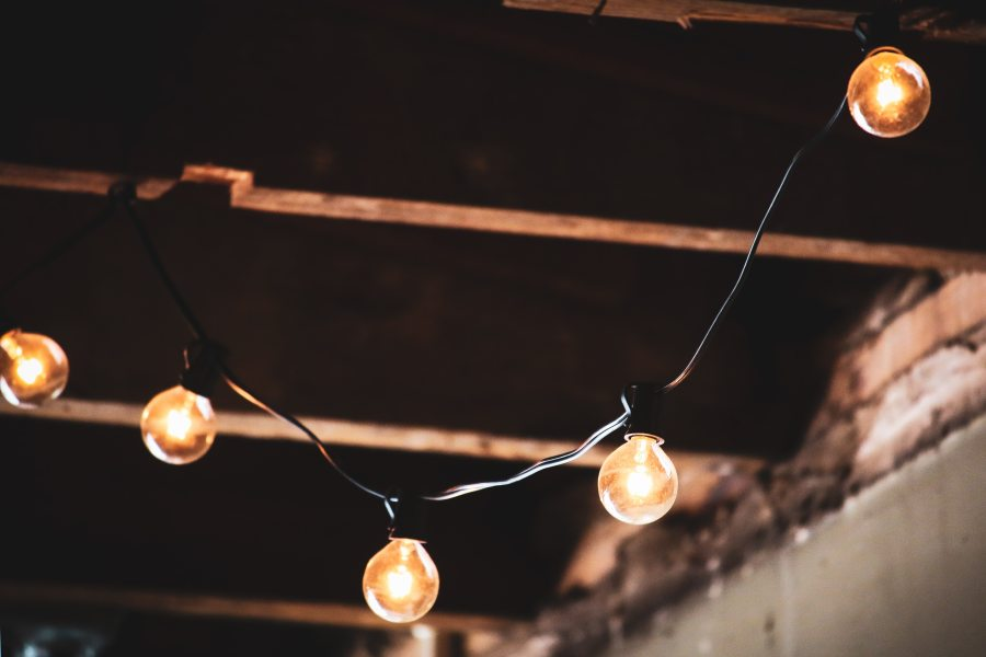 A string of lightbulbs against a brown beamed ceiling