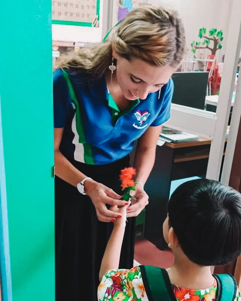 Teacher Chane getting a flower from one of her students.
