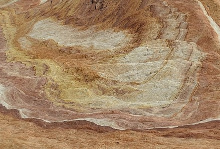 Rock layers in pink, white, light brown, and yellow