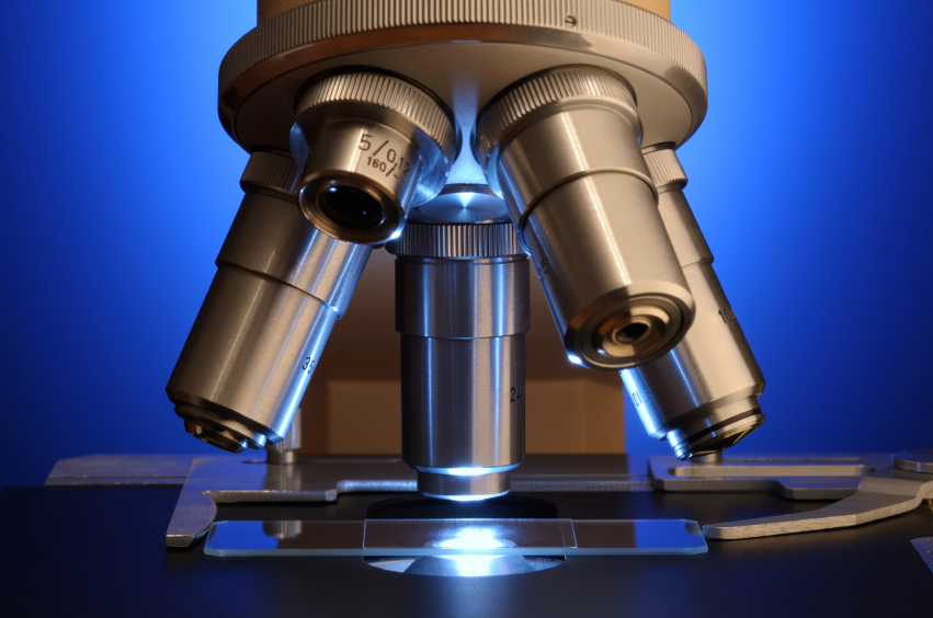Close up photo of microscope lenses over a slide, against a blue background