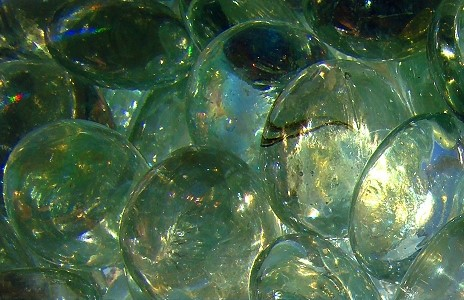 Transparent light green glass blobs with light coming from the lower right corner