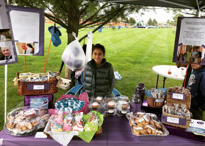 Alexandria Campillay at her bake sale table under a canopy, with photos of her family and grandfather