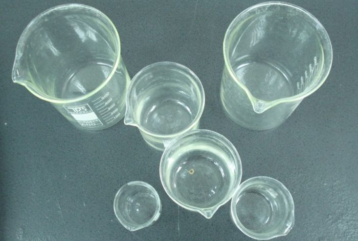 Clear glass beakers of differing sizes on a slate gray surface, viewed from above