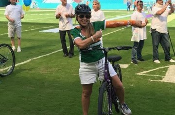 Camille Moses, pancreatic cancer survivor, prepares to ride her bike as part of the Miami Dolphins Cancer Challenge