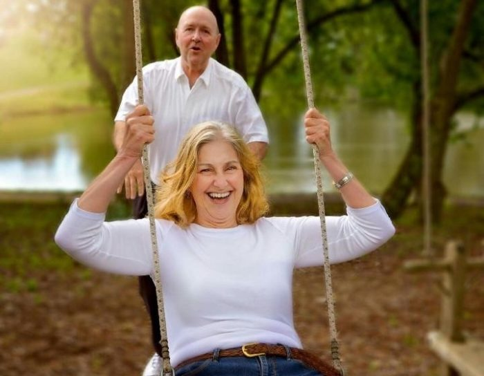 Susan Riddle on a swing, with her husband behind her