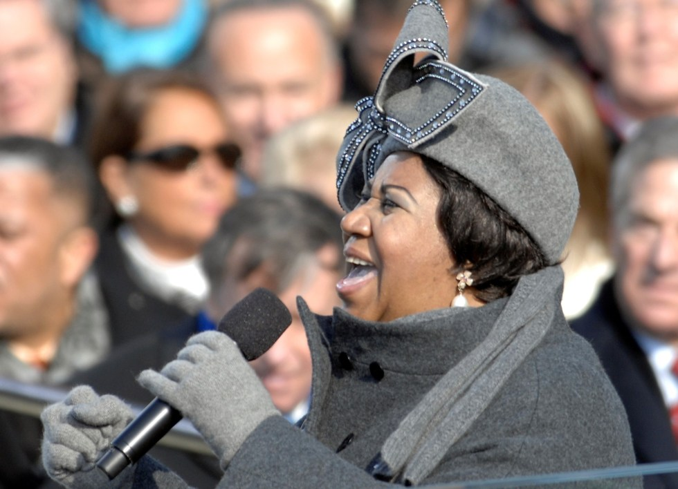 Aretha Franklin wears a gray coat and iconic gray hat with a large bow to sing at Barack Obama's 2009 inauguration as President of the United States