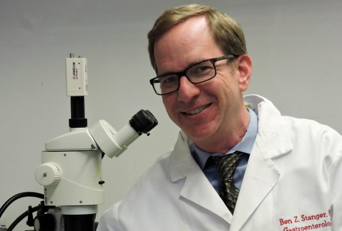 Dr. Ben Z. Stanger with a microscope in a lab