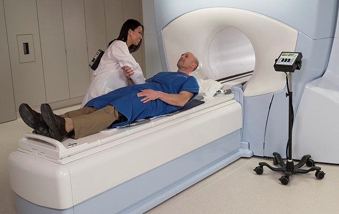 Female radiation oncologist and male patient at an MRI guided radiation machine