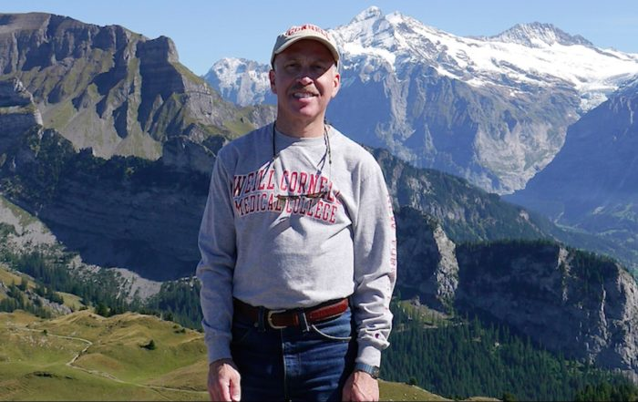 Steve Merlin, long-term survivor of pancreatic cancer, standing in a meadow with the mountains in the background
