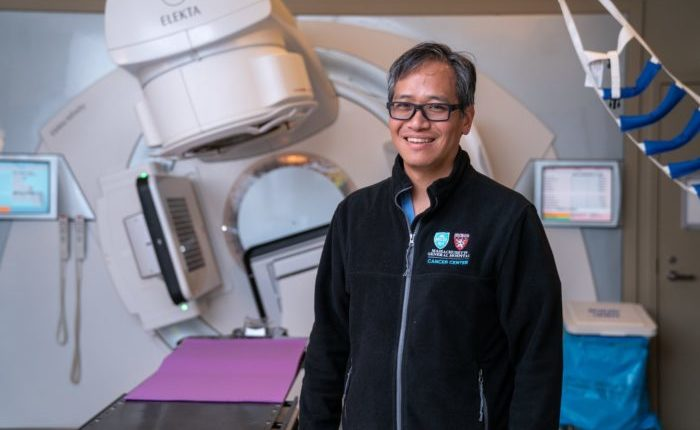 Dr. Theodore Hong stands in front of a radiation machine