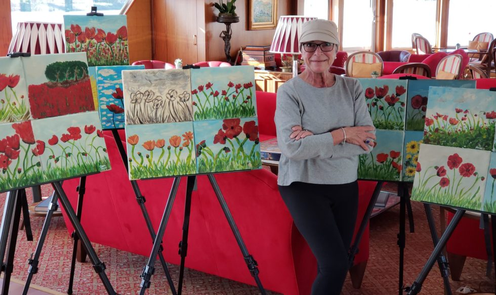 Pancreatic cancer patient Davi D'Agostino with student paintings on a river cruise ship