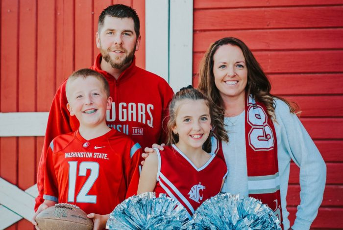 Andrea Barkstrom and her family in front of a red barn