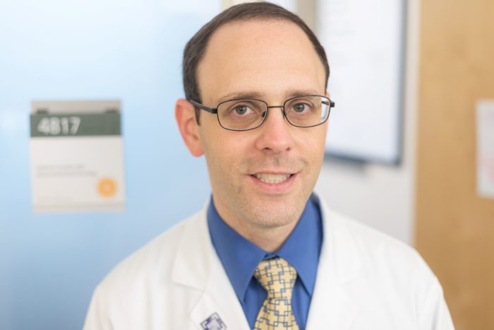 Dr. Andrew Coveler in a white coat and blue shirt, against an office background