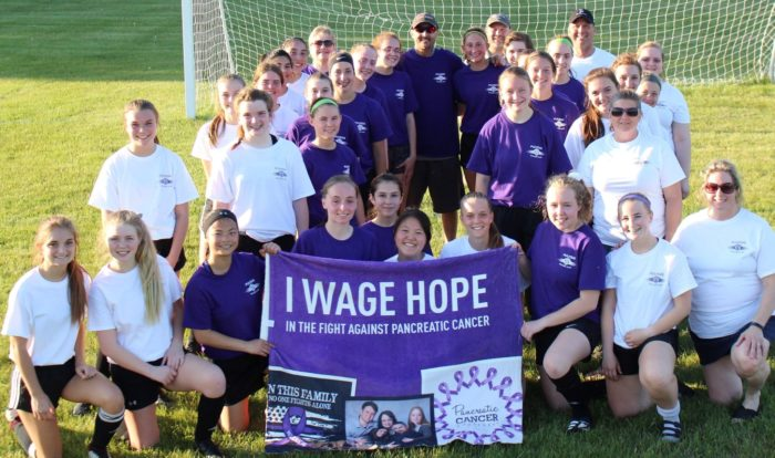 Pancreatic cancer patient Gregg Wittman surrounded by his soccer team, all in purple or white