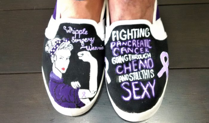 Black sneakers painted with purple sayings to encourage Sandy Robis