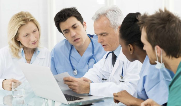 A group of doctors and medical professionals discussing a case
