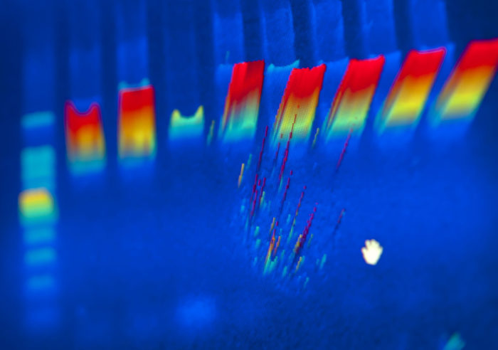 DNA scan of rainbow colors on a royal blue background