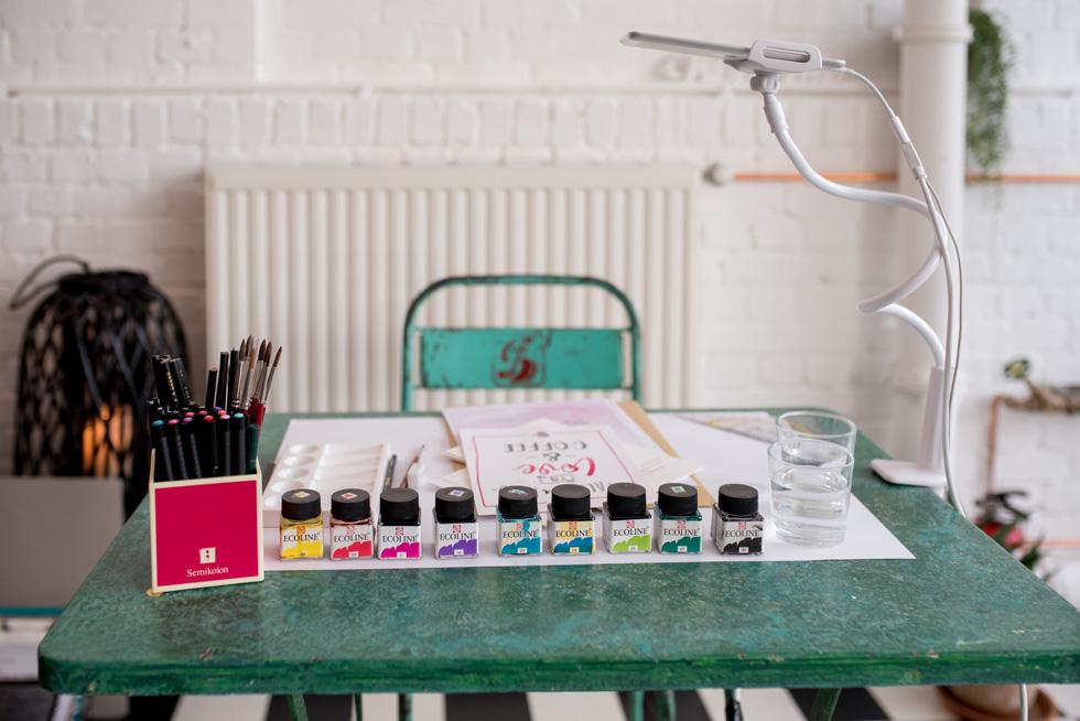 Watercolor Lettering mit Pinsel, Wasser und Ecoline Wasserfarben auf dem Tisch vorbereitet