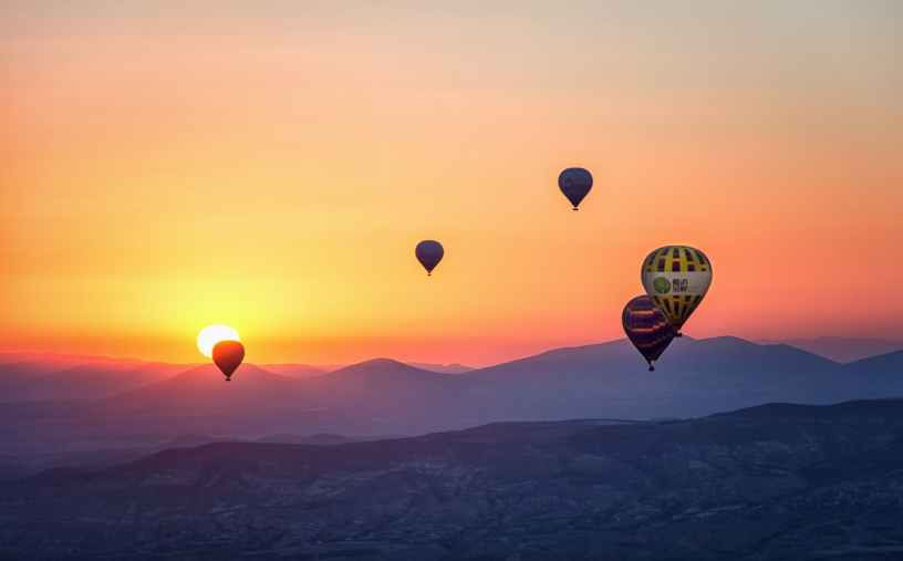 hot air balloons over mountains at sunset