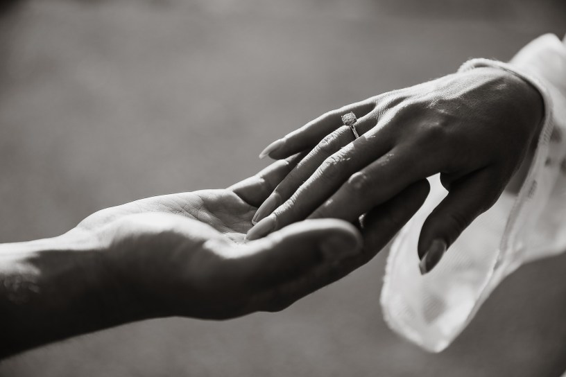 black and white photo of a bride and groom holding hands