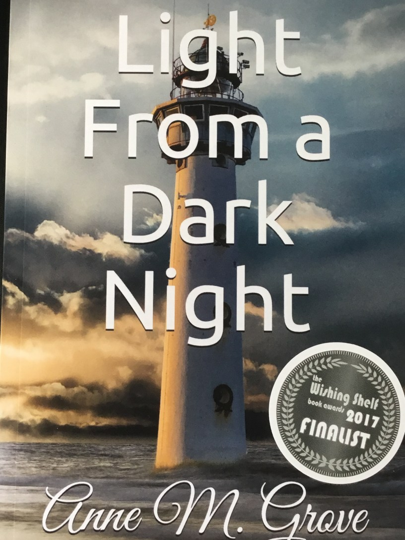 Book Cover, 'Light from a Dark Night' by Anne Grove. The Wishing Shelf finalist 2017 award sticker. The picture of a lighthouse after a storm. Light breaking through the storm clouds.