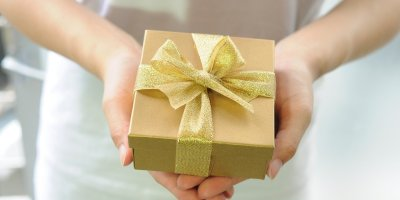 woman in white holding a gift box with gold ribbon